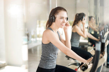 Pretty young sport woman is exercise on bicycle in gym, Healthy lifestyle