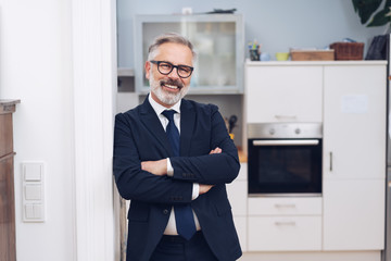 Smiling mature man in suit and glasses at home