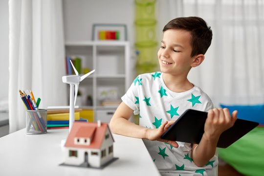 ecology, technology and energy saving concept - smiling boy with tablet pc computer, toy house model and wind turbine at home