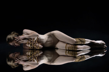Young seductive slim woman lying on mirror floor tied with decorative knots of natural jute rope. Ancient Japanese art of aesthetic bandage and tying shibari kinbaku. Sexual games concept.