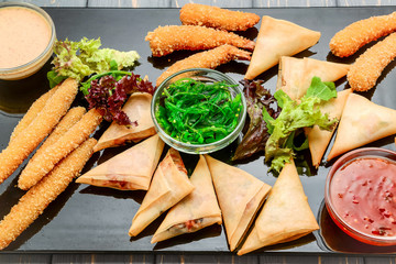 Many types of savoury snack with different sauces and salads