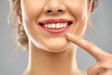 oral care, dental hygiene and people concept - close up of finger pointing to woman face with healthy white teeth over gray background