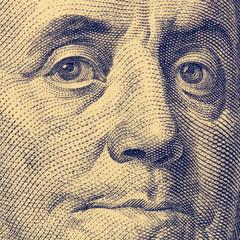 Fragment of hundred dollar bills. Franklin's face, square format, toned.