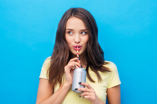 people concept - smiling young woman or teenage girl in yellow t-shirt drinking soda from can through paper straw over bright blue background