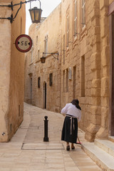 A nun brushing the street in Malta