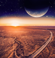 Unreal landscape - dark planet over road winding through desert landscape at sunset. Elements of this image are furnished by NASA