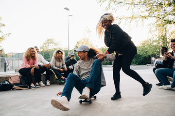 Teenage girl pushing young man on skateboard while friends laughing at park