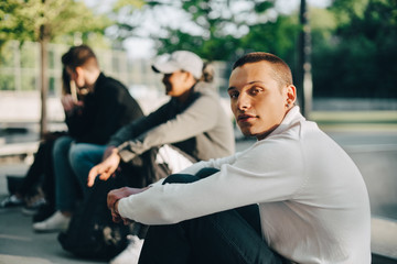 Portrait of young man sitting with friends at park