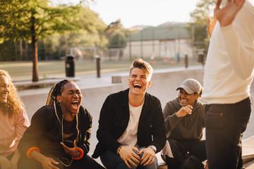 Cheerful multi-ethnic friends talking at skateboard park