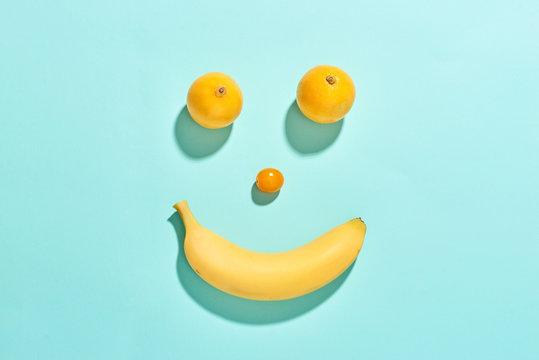 Happy fruit face with banana, tomato and lemons isolated on blue background