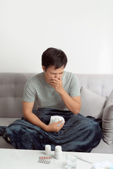 Man feeling cold, lying in the sofa and blowing his nose