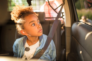 Girl looking through window while sitting in electric car