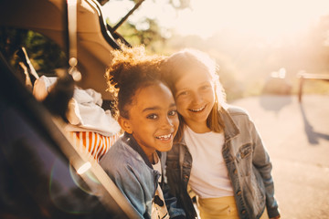 Portrait of smiling multi-ethnic girls in car trunk during picnic