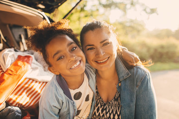 Portrait of smiling girl with arm around mother sitting in car trunk during picnic