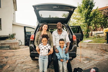 Portrait of happy family sitting in car trunk