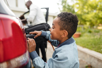 Side view of boy looking while charging electric car