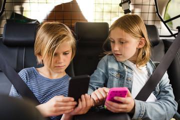 Blond siblings using smart phones while sitting in car