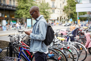 Side view of mid adult businessman using smart phone while standing by bicycles in city