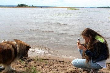 Girl taking pictures of a dog on the river Bank