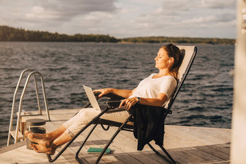Full length of woman relaxing on deck chair at jetty over lake