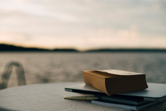 Close-up of laptop with books on table against lake