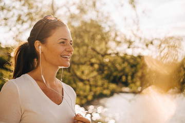 Smiling mature woman talking through headphones in summer vacation