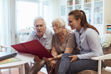 Young woman with senior couple looking photo album at home