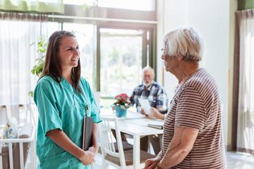 Young nurse talking with senior woman at nursing home