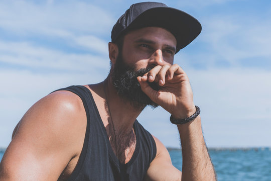Bearded man model wearing black cap and tshirt looks away, sunset in the sea scenery