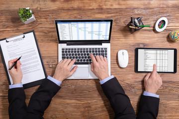 Businessman Doing Multitasking Work In Office