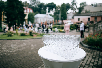 many glasses for champagne in wedding ceremony in park