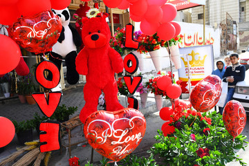 Youngsters look at a red teddy bear outside a shop selling Love signs, chocolate and flowers on Valentines Day in Gaza City