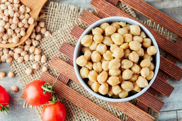 Cooked chickpeas (Cicer arietinum) in bowl on wooden background