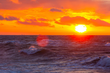 bright orange sun in a cloudy sky over the sea during sunset