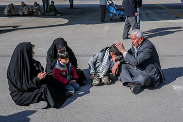 Relatives of members of Iran's elite Revolutionary Guards, who were killed by a suicide car bomb, mourn at Isfahan airport