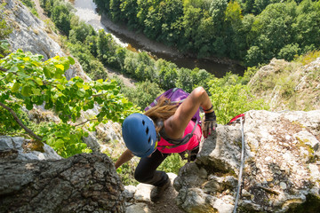 "Woman tourist climbing a via ferrata route called ""Casa Zmeului"", in Vadu Crisului, Apuseni mountains, Romania, above a meandring river, with a railroad track alongside it, on a hot Summer day"