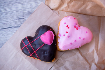 Heart shape Doughnut over the brown paper bag on the wooden table. The closeup food photo.