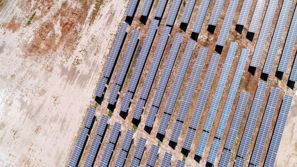 top aerial view of solar panels in energy farm in desert