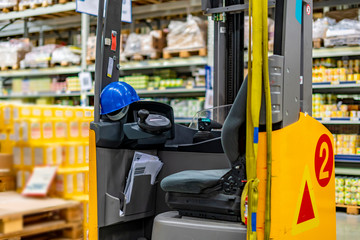 empty forklift loader at a warehouse with blue helmet b
