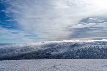 The low clouds over high mountains at winter day.