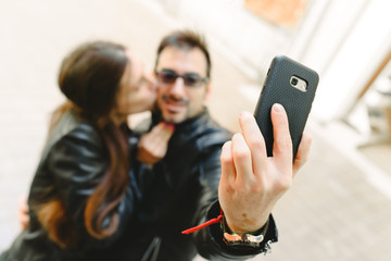 Couple in love doing a self-portrait selfie with the mobile phone.