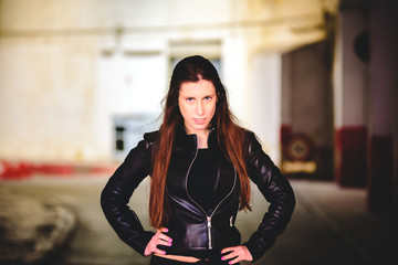 Portrait of young female model dressed in black leather posing casually in an urban setting.