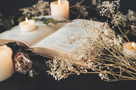 Close up of open vintage poetry book decorated with dried baby's breath flowers. Blurred background with white lit burning candles, plants and small sage stick. Black table surface. Romantic soft feel