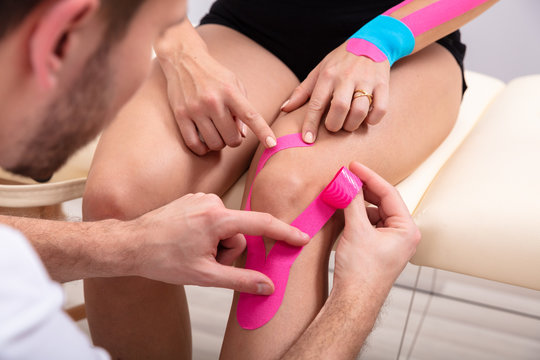 Man Applying Kinesiology Tape On Woman's Knee
