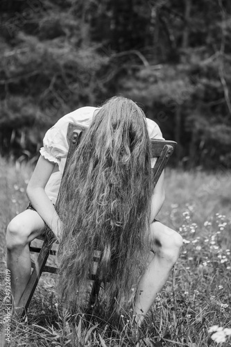 The girl covered her face with her hair sitting on a chair