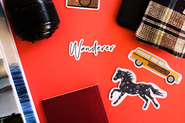 Books, camera lens, handphone, passport, coin sack with a picture of a horse, car , camera and a word wanderer as symbols for travel shot on a plain isolated red background as wallpaper.