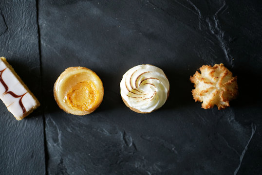 Top view of delicious French mini cakes lined up on black slate