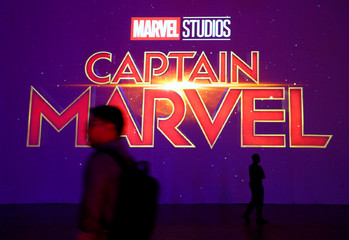 A man is silhouetted against the Captain Marvel logo at a fan event in Singapore