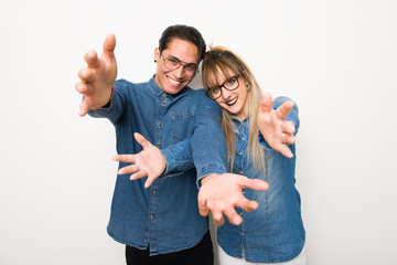 Young couple with glasses presenting and inviting to come with hand