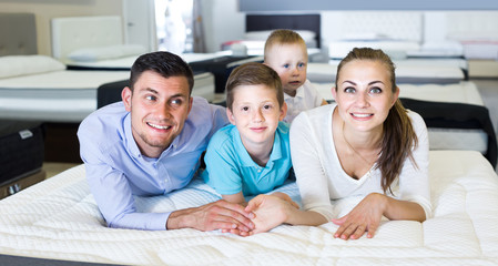 parents with two young sons testing mattress in store